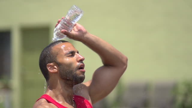 A man pouring water over his head and resting after a intense workout. - Super Slow Motion - filmed at 240 fps