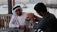 CU MS Man pours tea for his Arab friend in outdoor restaurant/Dubai/UAE