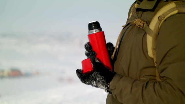 Man pours tea from a thermos winter