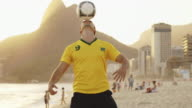 MS A man practices tricks with a football on Ipanema Beach / Rio de Janeiro, Brazil