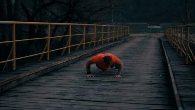 Man practicing pushups on the bridge
