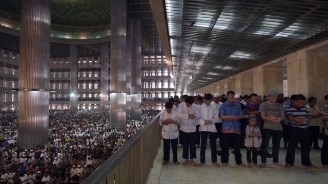 MS man praying with raised hands WS RL men praying on upper balcony of Istiqlal Mosque to large full hall of men praying MS men sit in prayer on an...