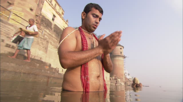 A man prays and performs ablutions in a temple river in  India.