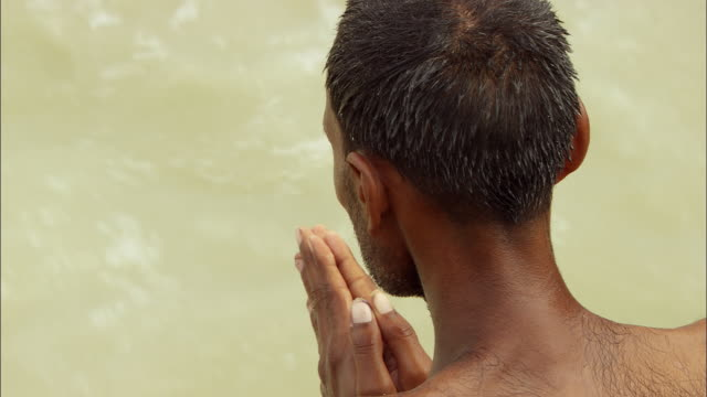 A man prays in the Ganges River. Available in HD.