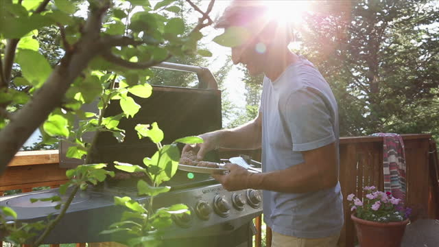 Man prepares barbeque for cooking, then adds meat patties