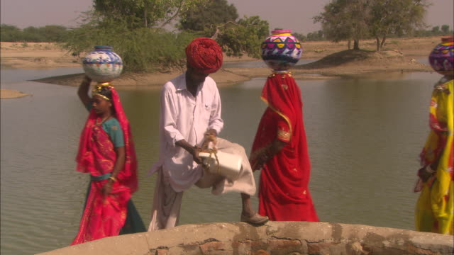 Man prepares to lower container into well as women wearing brightly coloured saris pass by carrying water filled urns on heads Rajasthan Available in HD.