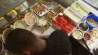 HA MS Man preparing falafel sauces and vegetables in diner / Berlin, Germany