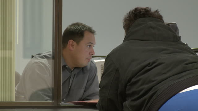 Man processing customer's paperwork at counter in job center/ Antioch California USA/ AUDIO
