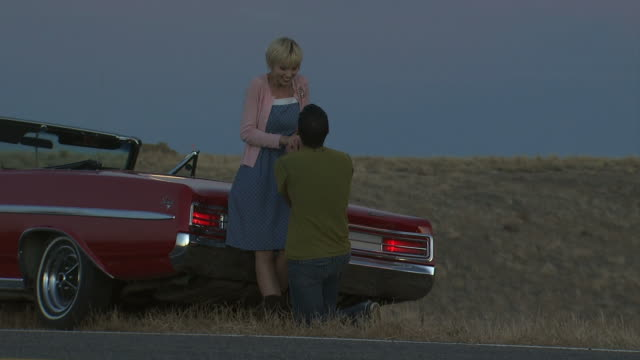 man proposing to a woman on the side of the road