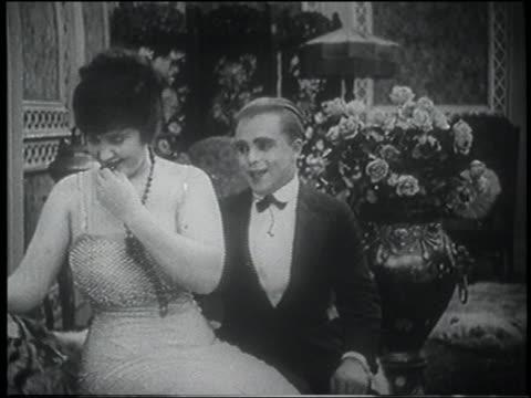 B/W 1916 man puckering lips at woman, she starts to kiss him but turns away embarrassed (jump cut)