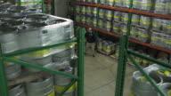 Man pulling a pallet jack full of beer kegs