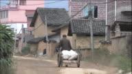 A man pulls a cart up a street.