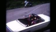 1966 man pulls away in white convertible