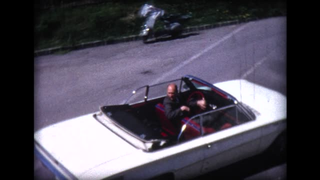 1966 man pulls away in white convertible
