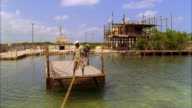 Man pulls ferryboat across river then passenger with bike disembarks, Belize Available in HD.