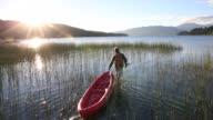 Man pulls kayak through marsh, then paddles, sunrise