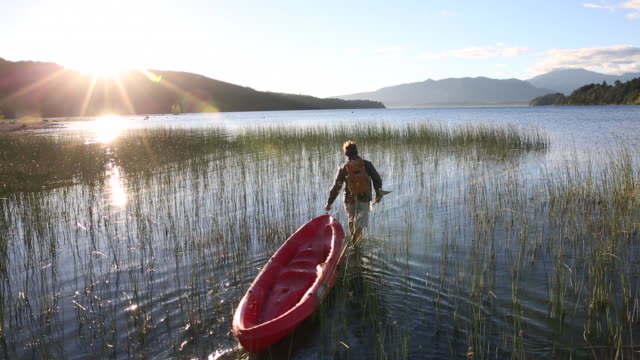 Man pulls kayak through marsh, then paddles, sunrise