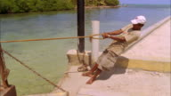 Man pulls rope to dock timber ferry and ties it off, Belize Available in HD.