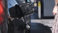 A man pumping gas, focus on hand