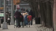 A man pushes all his belongings in a shopping cart on a Manhattan Street