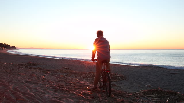 Man pushes bike along beach at sunrise, looks over sea