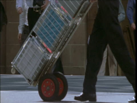 Man pushes trolley with boxes through busy street, Sydney