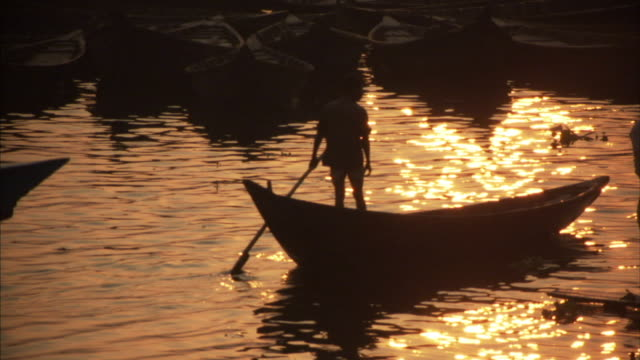 MS, Man pushing his boat with oar on river at sunset, Dhaka, Bangladesh