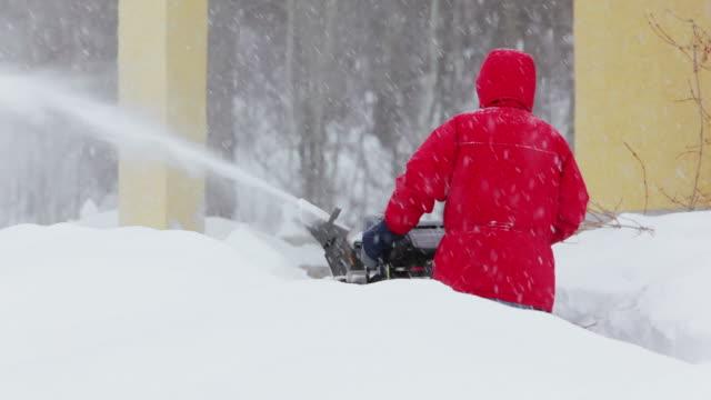 Man pushing snow blower