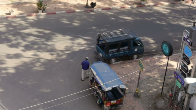 Man pushing Tuk Tuk away in Vientiane, Laos