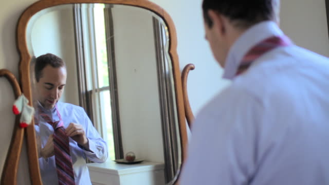 Man putting on tie with reflection in mirror
