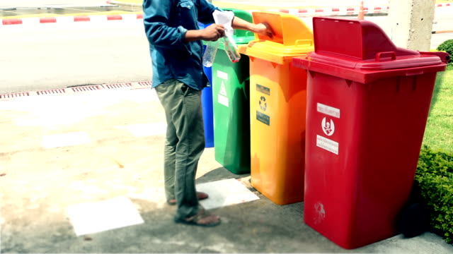 Man putting plastic bottles in recycle container.