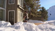Man putting shovel down and brushing snow off his clothes / Ketchum, Idaho, United States