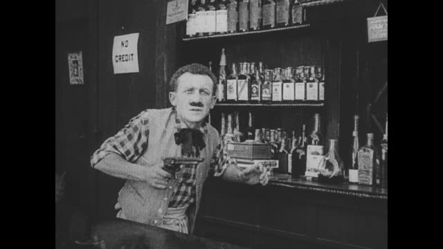 Buster Keaton raises a sign that reads 'bartender needed' after Wild Bill Hiccup shoots the bartender