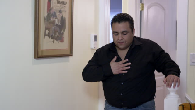 Man reaching the top of the stairs having trouble breathing.