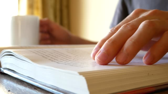 man reading a book, turning pages, and slide his hand to find something - close up view