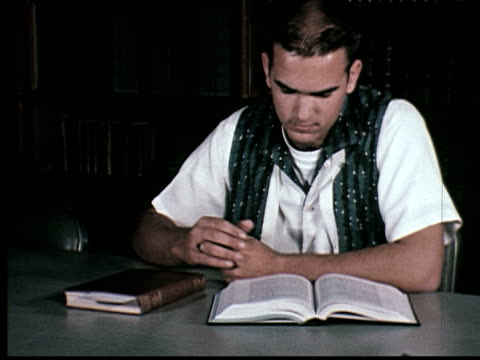 Man reading book then pamphlet in library, USA, MS