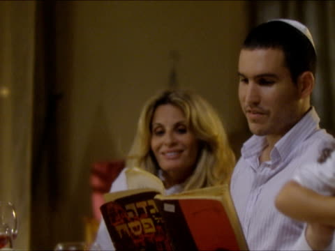 CU PAN Man reading from prayer book, sitting at dinner table at Seder Night during Passover / Beit Yitzhak, Israel