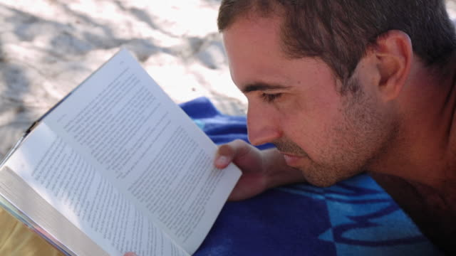 A man reading in the beach, at Noosa, Queensland, Australia