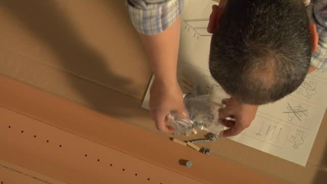CU HA Man reading instruction and arranging screws, London, England