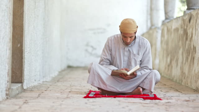 HD DOLLY: Man Reading Koran At Mosque Corridor