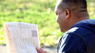 Man reading newspaper, looks over shoulder at camera