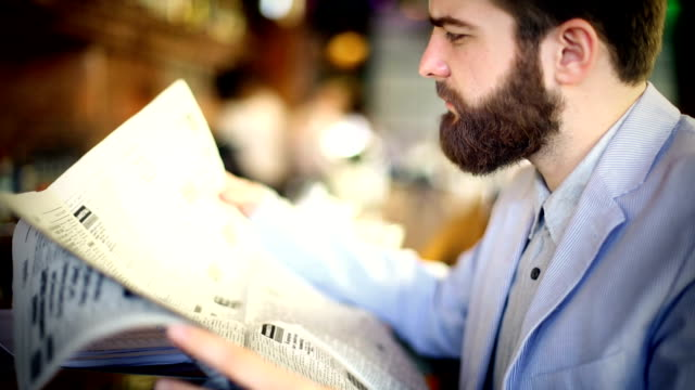 Man reading newspapers.