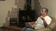 Man reads newspaper sitting in the armchair