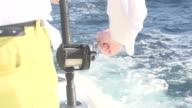 Man Reeling In Line On Boat