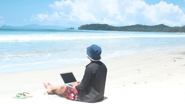 Mann Entspannen Sie sich und spielen laptop am Strand