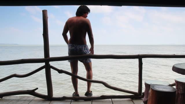 Mann Entspannen Sie sich auf dem Balkon und springen ins Meer