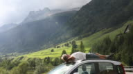 Man relaxes on car roof, below mountains and clouds