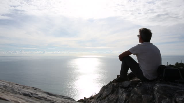 Man relaxes on cliff edge above distant sea, time lapse