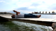 Man relaxes on wooden walkway, uses smart phone