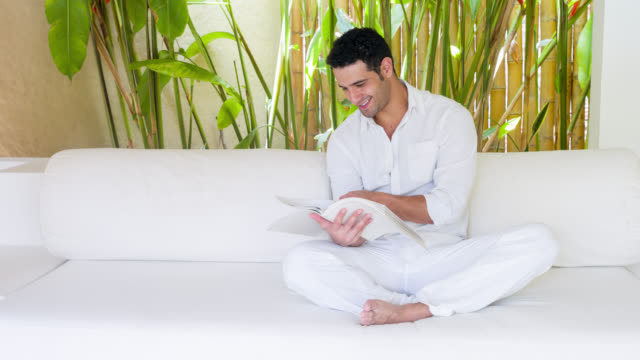 Man relaxing and reading a book at a hotel